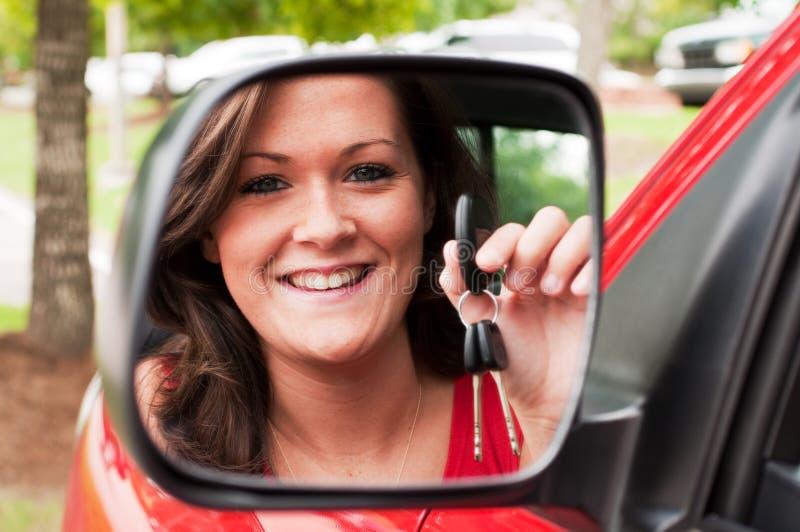 la holding attraente del brunette imposta il veicolo dello specchio fotografia stock libera da diritti