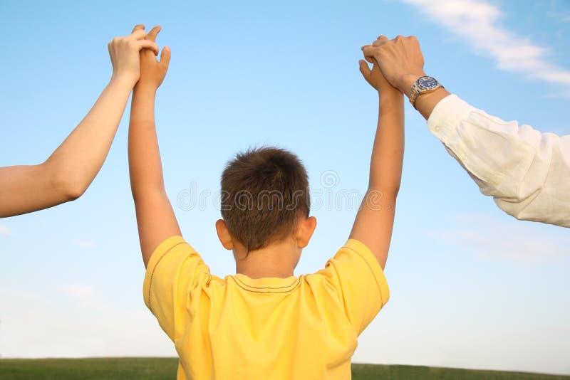 La holding del ragazzo parents le mani fotografia stock