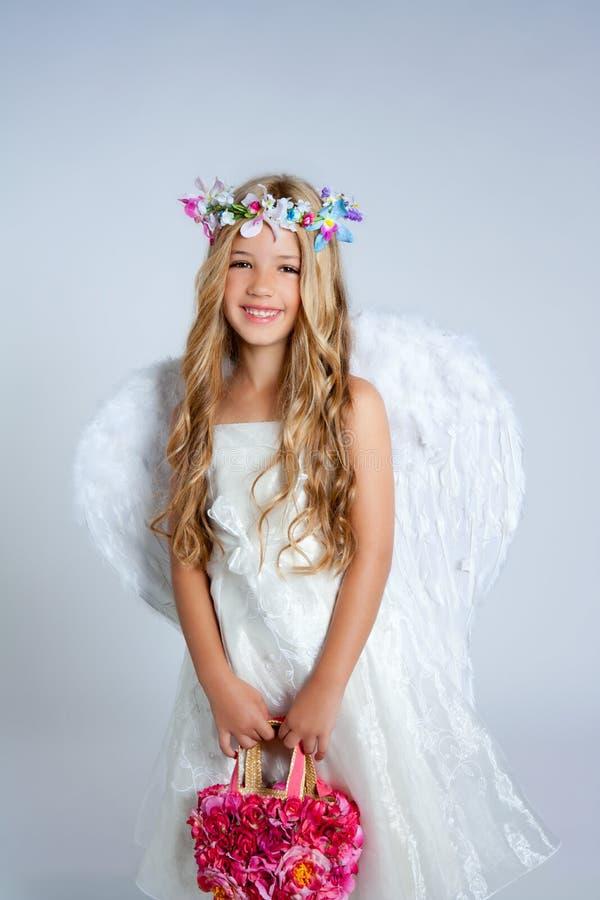 La holding della ragazza dei bambini di angelo fiorisce il sacchetto con le ali fotografie stock