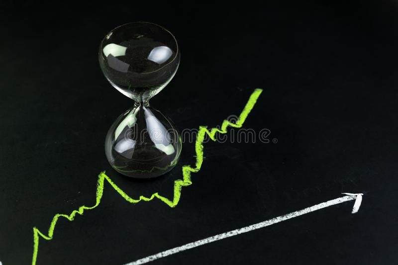 La hora para invierten o el concepto de la inversión a largo plazo, el reloj de arena o los sandglass con el interior negro de la foto de archivo