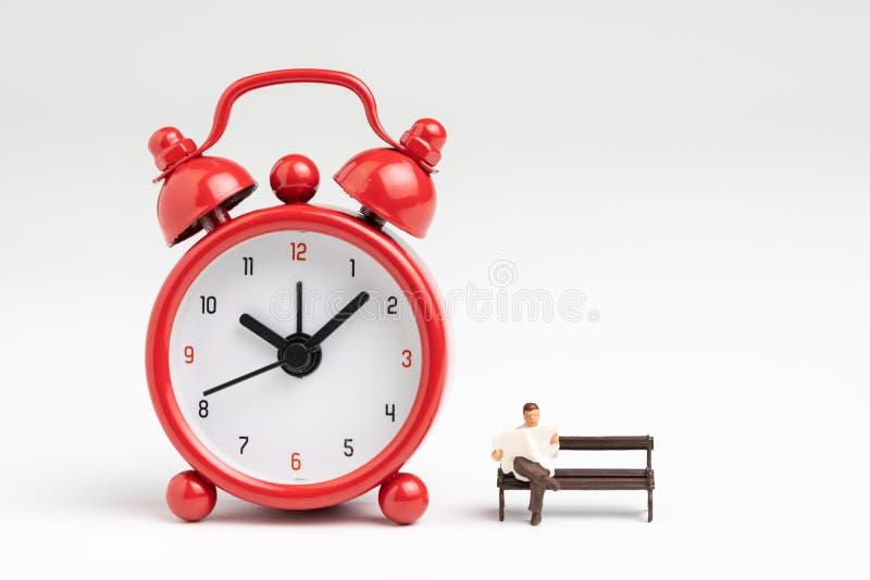 La hora que cuenta abajo para la carrera, procrastina o concepto feliz del retiro, viejo hombre mayor feliz miniatura que se sien imagen de archivo libre de regalías