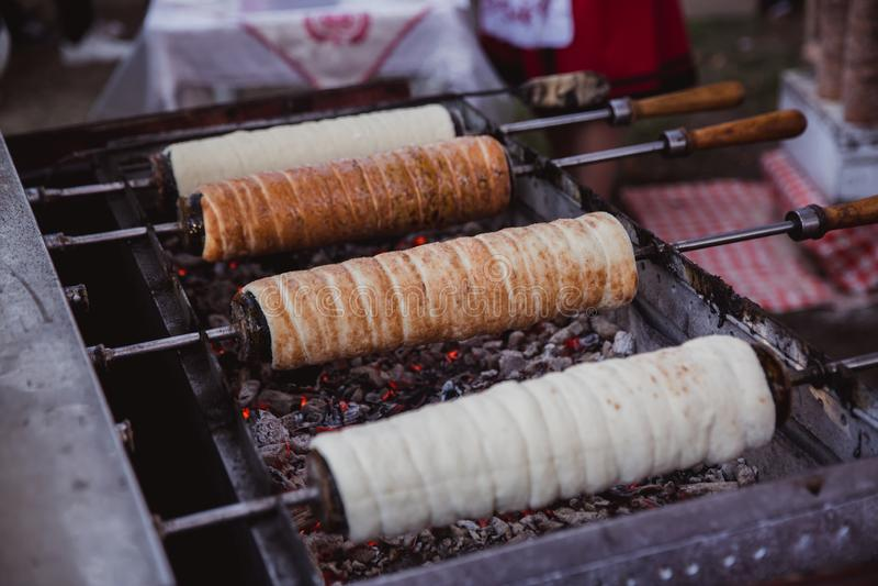 La hornada de Kurtoskalacs, la torta húngara tradicional del escupitajo, en una tienda de pasteles Festival (½ del ¿de Fesztivï d fotos de archivo libres de regalías