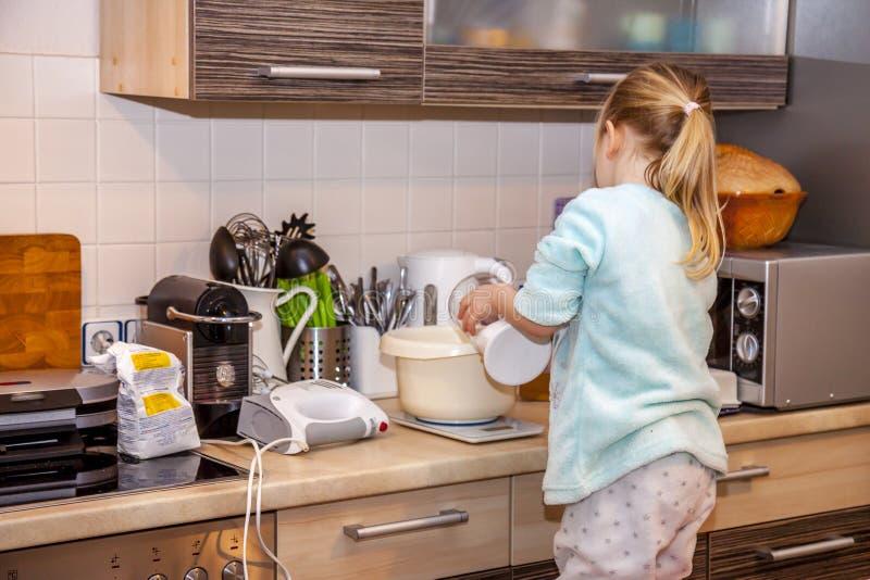 La hornada de la niña se enrolla en la cocina después de una receta en el smartphone imagenes de archivo