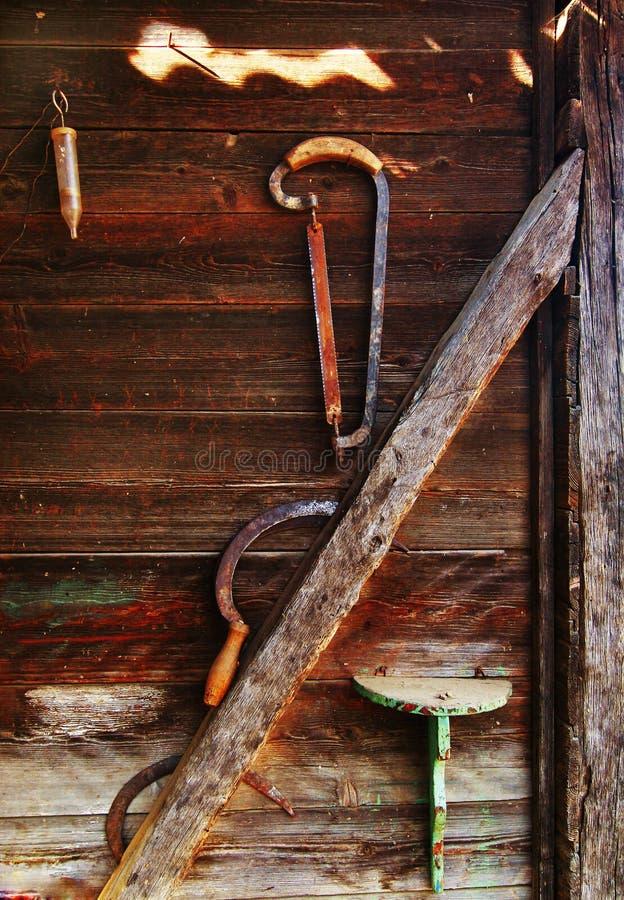 La hoz y vio en la pared de madera imágenes de archivo libres de regalías