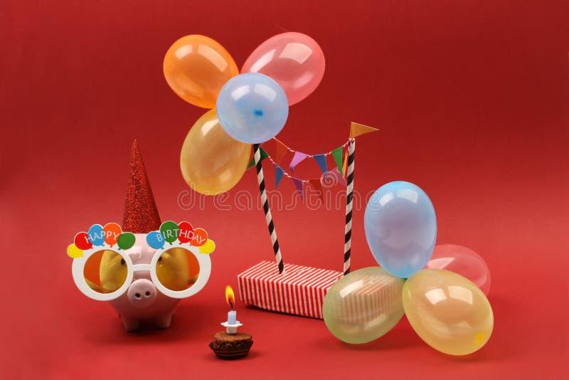 La hucha con feliz cumpleaños de las gafas de sol, el sombrero del partido y el partido multicolor hincha en fondo rojo fotos de archivo libres de regalías