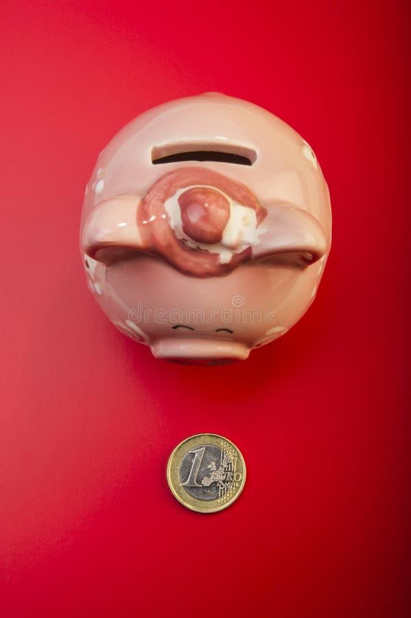 La hucha y acuña un euro en un fondo rojo cubierta imagenes de archivo