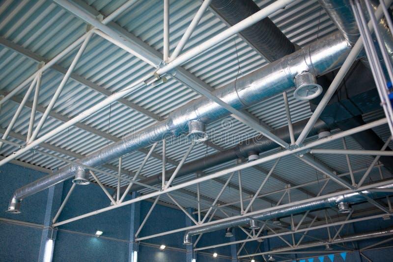 La HVAC canaliza la limpieza, tubos de la ventilación en la ejecución de plata del material de aislamiento del techo dentro del n fotografía de archivo libre de regalías