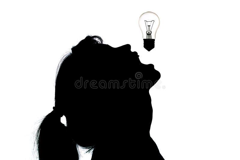 La idea creativa, la silueta de una mujer que abrió su boca para comer una bombilla que simboliza pensamiento o la innovación úti foto de archivo