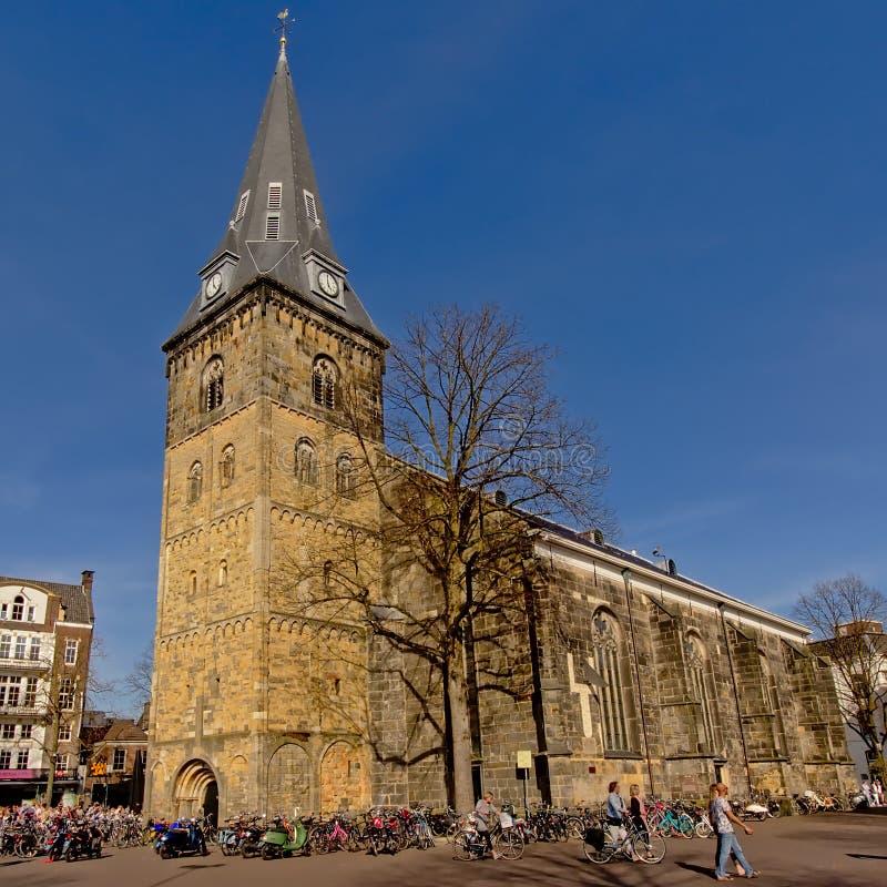 La iglesia de Enschede, los Países Bajos con el andd de mucha gente monta en bicicleta alrededor imagenes de archivo