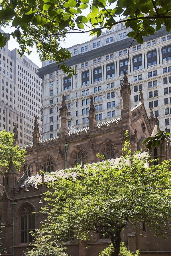 La iglesia de la trinidad hermosa ocultada entre los rascacielos de Manhattan, Nueva York, los Estados Unidos de América fotos de archivo
