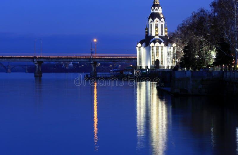 La iglesia hermosa con la iluminación en la noche del otoño, luces reflejó en el río Dnieper imagen de archivo