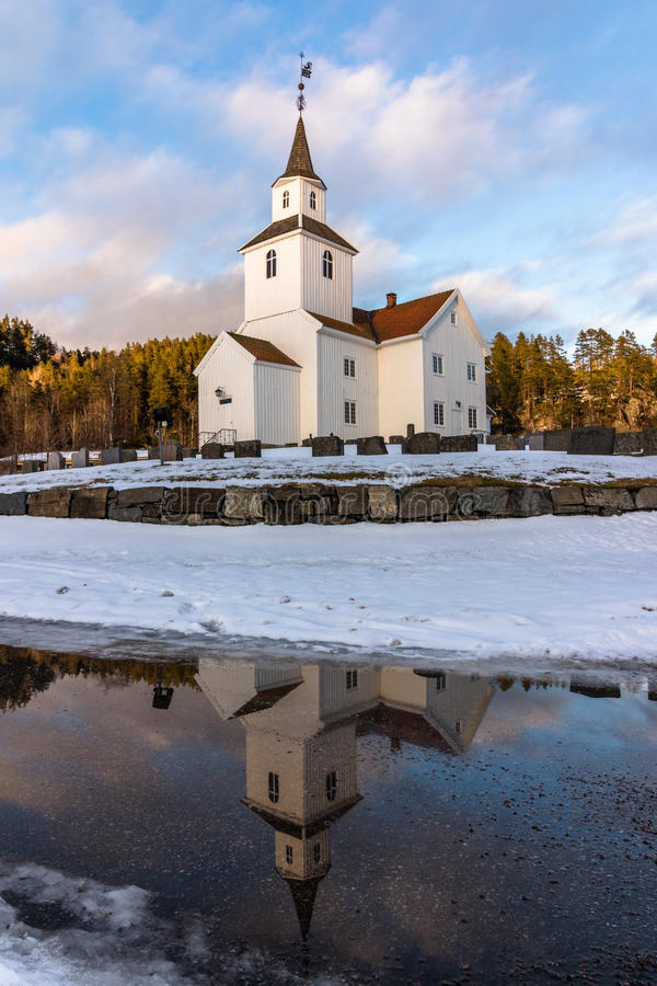 La iglesia reflejó en agua, invierno, nieve y cielo azul en Iveland Noruega, vertical imágenes de archivo libres de regalías