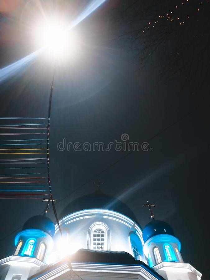 La iglesia turística popular en la iluminación de las luces de la noche en Zhytomyr, brunches del cielo nocturno de Ucrania cruza imagen de archivo libre de regalías
