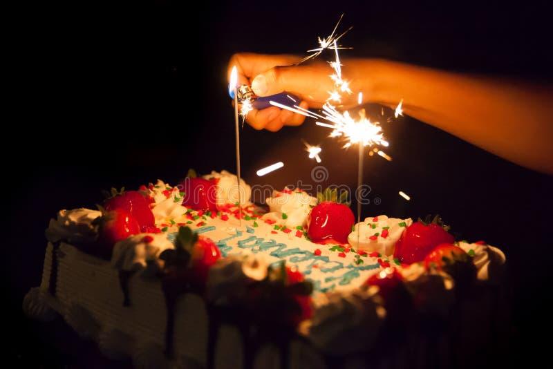 La iluminación chispea en una torta de cumpleaños imagenes de archivo
