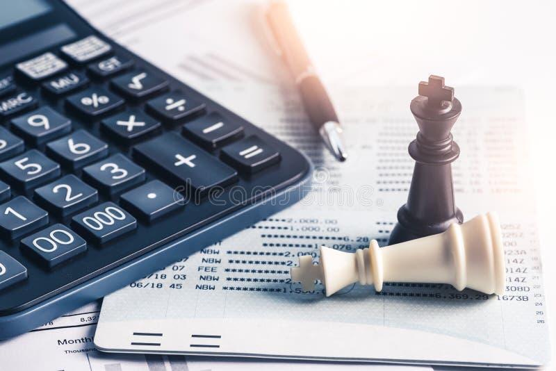 La imagen abstracta de los ambos reyes blancos y negros del ajedrez que ponen en el documento de contabilidad y una calculadora,  imagenes de archivo
