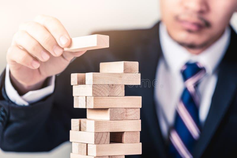 La imagen abstracta del hombre de negocios coloca uno de los ladrillos del edificio en el top de la torre foto de archivo libre de regalías
