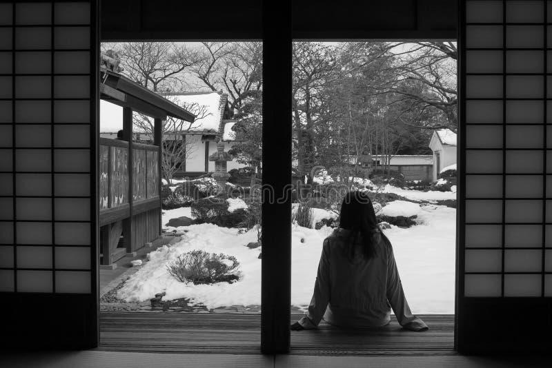 La imagen blanco y negro abstracta de la sentada sola de la mujer se relaja en terraza de madera y la mirada adelante al parque j foto de archivo