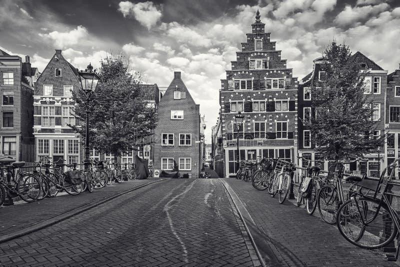 La imagen blanco y negro de bicicletas parqueó en un puente a través del th imagen de archivo