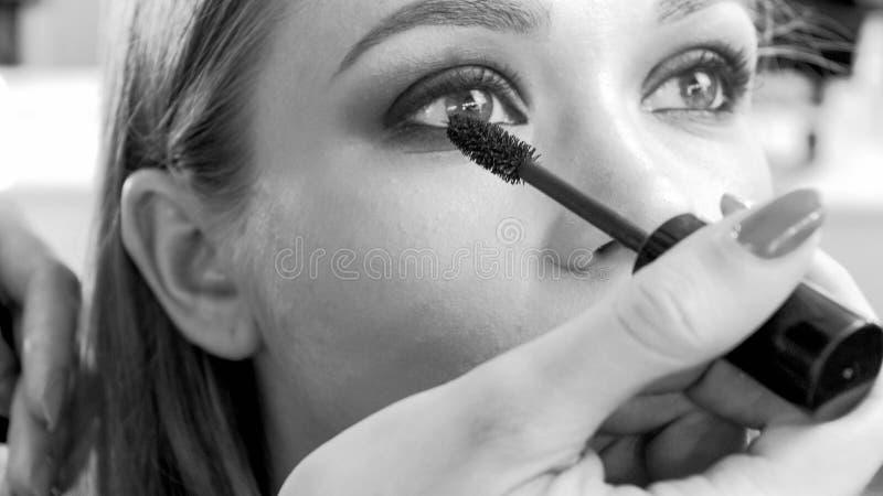 La imagen blanco y negro del ` profesional s del modelo de la pintura del artista de maquillaje observa con rimel foto de archivo