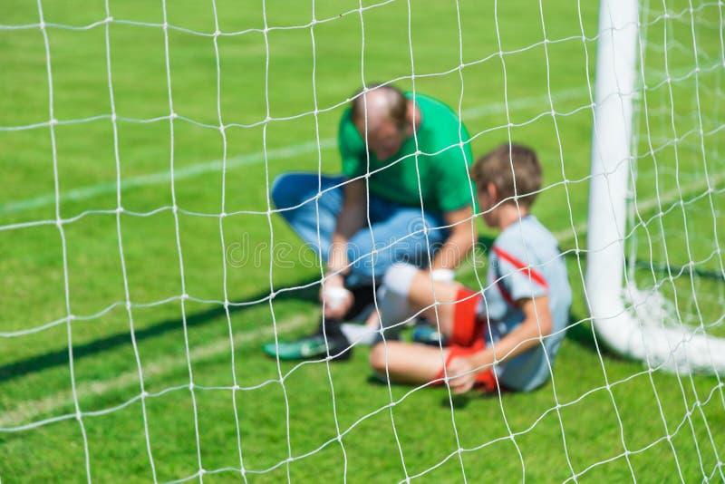 La imagen borrosa de un joven hirió el playe masculino del fútbol o del fútbol imagen de archivo libre de regalías