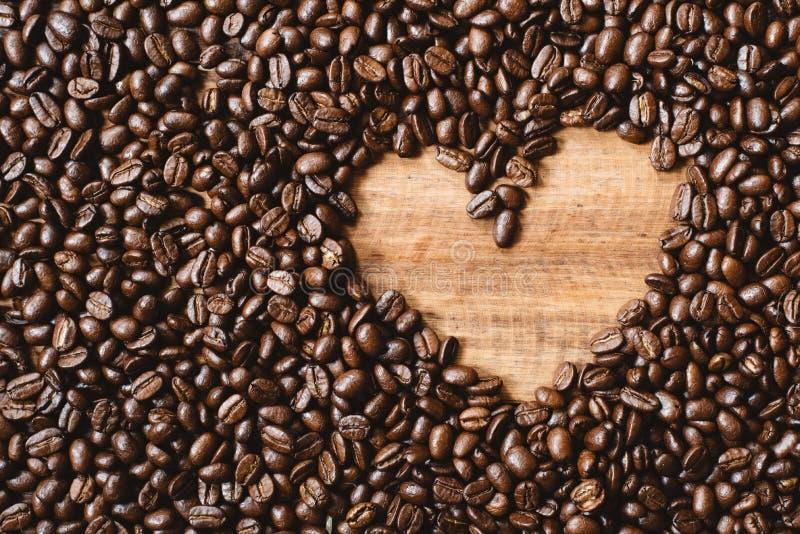 La imagen completa del marco de la oscuridad fresca asó los granos de café con el espacio de la copia de la forma del amor imagenes de archivo