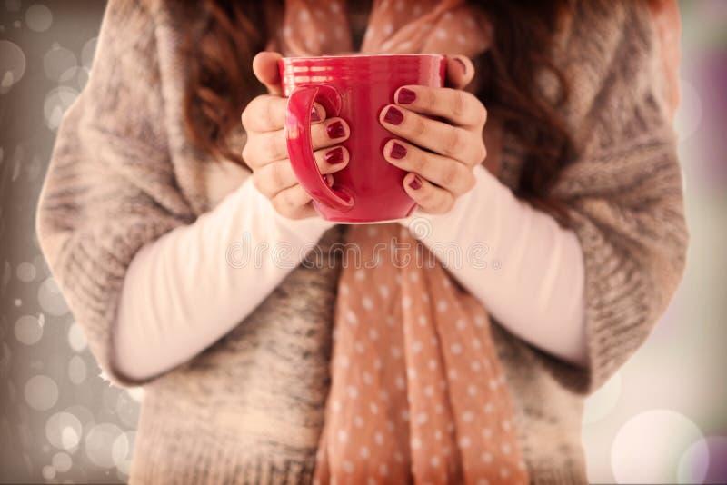 La imagen compuesta de la mujer en invierno viste llevar a cabo una bebida caliente imagen de archivo