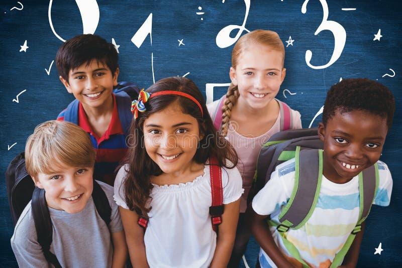 La imagen compuesta de la sonrisa poca escuela embroma en pasillo de la escuela imágenes de archivo libres de regalías