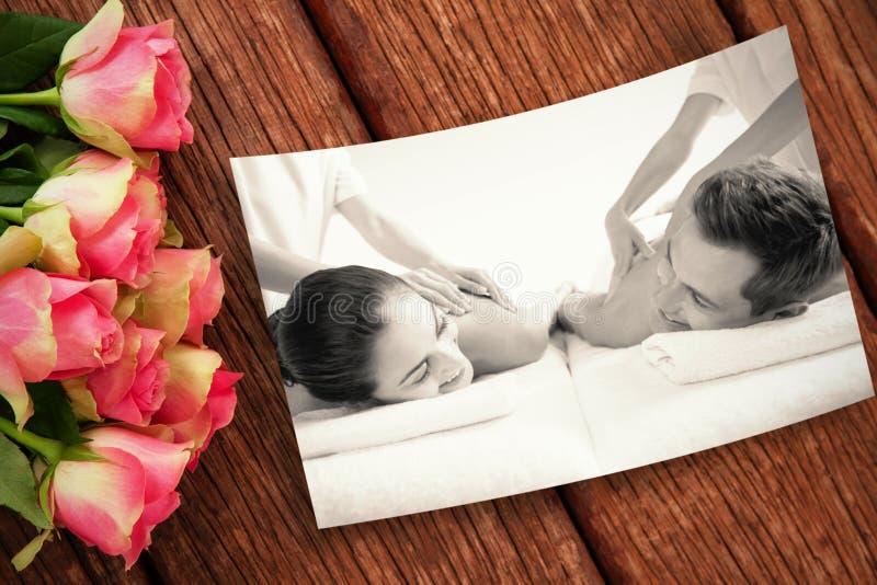 La imagen compuesta de los pares pacíficos que disfrutan de pares da masajes al poolside foto de archivo libre de regalías