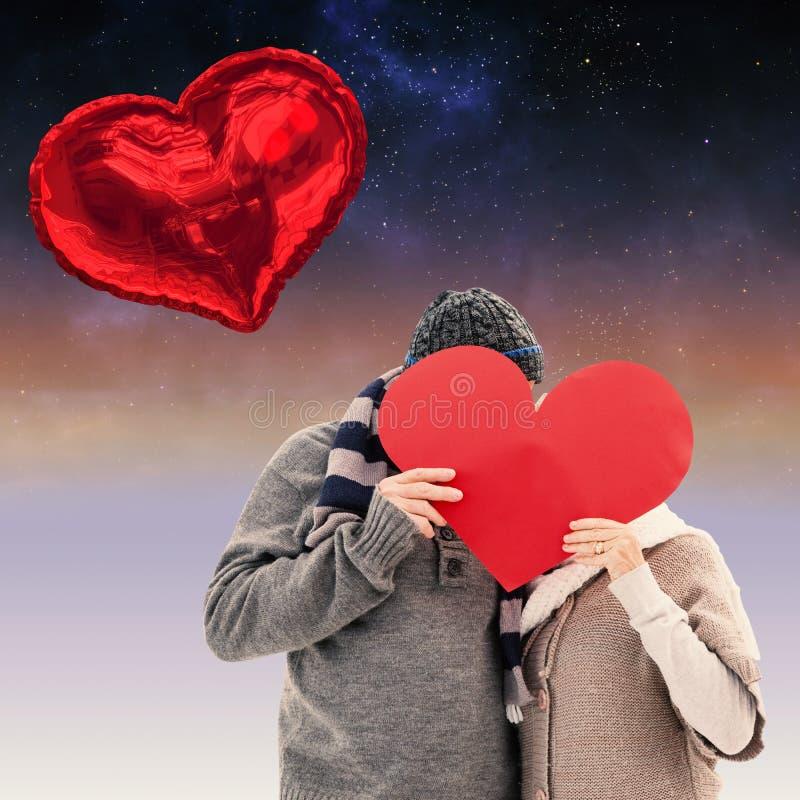 La imagen compuesta de pares maduros felices en invierno viste llevar a cabo el corazón rojo imágenes de archivo libres de regalías