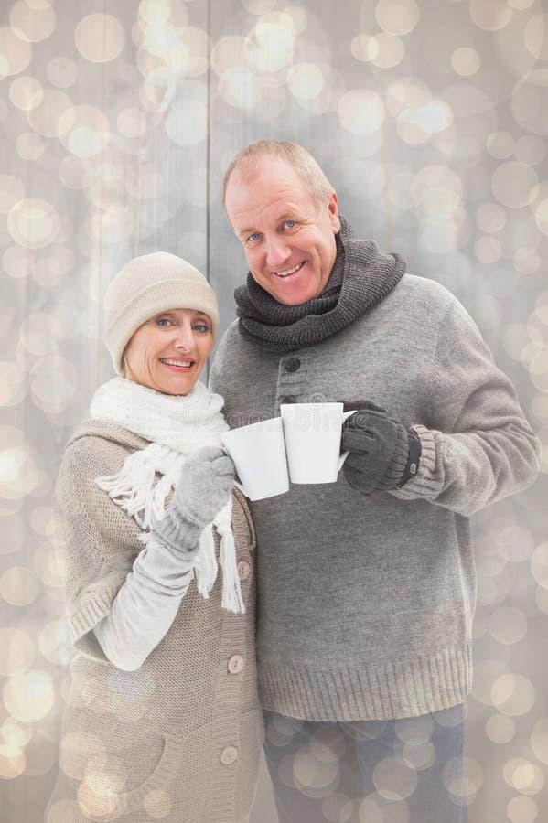 La imagen compuesta de pares maduros felices en invierno viste sostener las tazas fotografía de archivo libre de regalías