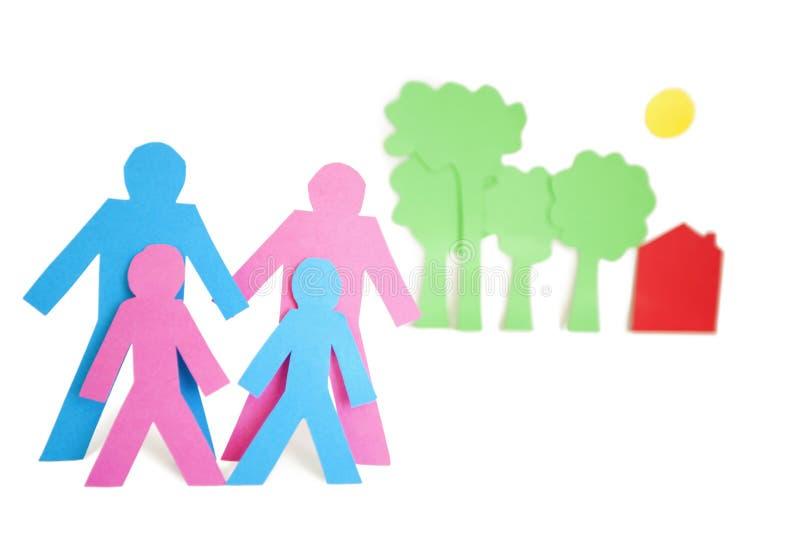 La imagen conceptual del papel cortó las formas que representaban una familia con los árboles y la casa sobre el fondo blanco fotos de archivo libres de regalías