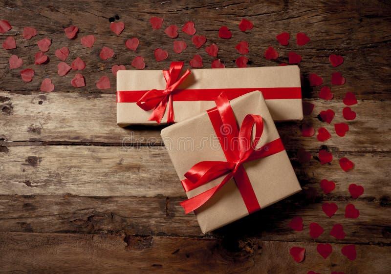 La imagen conceptual del santo feliz día de San Valentín envolvió los regalos y los corazones rojos en la tabla de madera del vin imagen de archivo libre de regalías