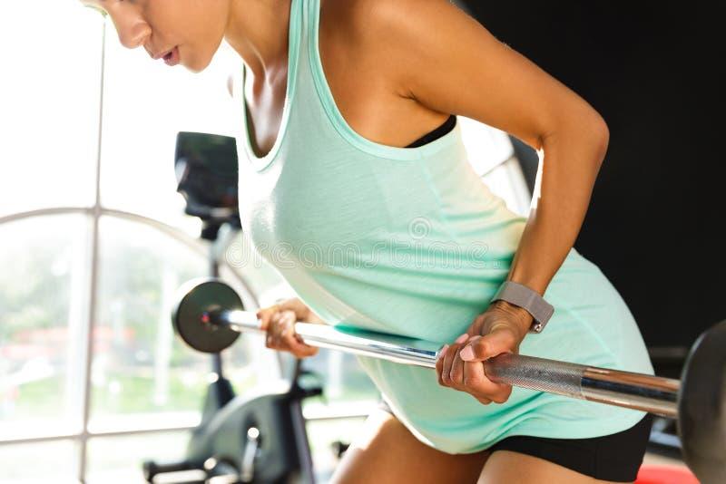 La imagen cosechada de la calma se divierte a la mujer que hace ejercicio con el barbell imagen de archivo