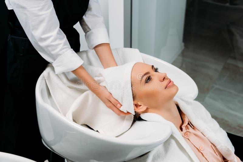 la imagen cosechada de la sequedad del peluquero lavó el pelo del cliente fotos de archivo libres de regalías