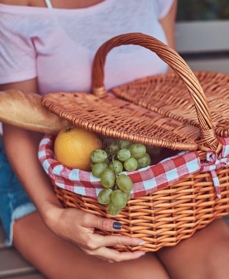 La imagen cosechada de una hembra que lleva la ropa casual sostiene una cesta de la comida campestre mientras que se sienta en un imágenes de archivo libres de regalías