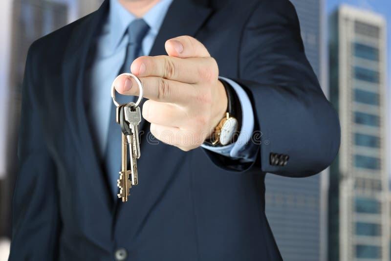 La imagen cosechada del agente de la propiedad inmobiliaria que da la casa cierra afuera foto de archivo