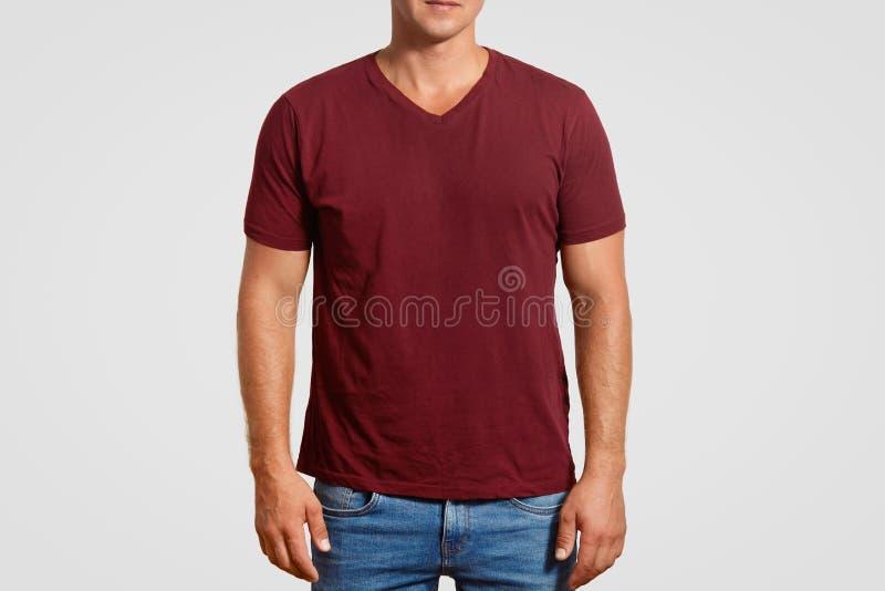 La imagen cosechada interior del hombre joven muscular en camiseta roja y de los vaqueros, soportes contra el fondo blanco, prese foto de archivo
