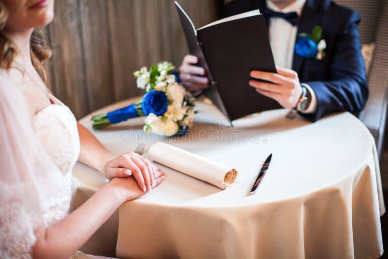 La imagen de Croped de los recienes casados que se sientan en la tabla en el café, novio mira el menú foto de archivo libre de regalías