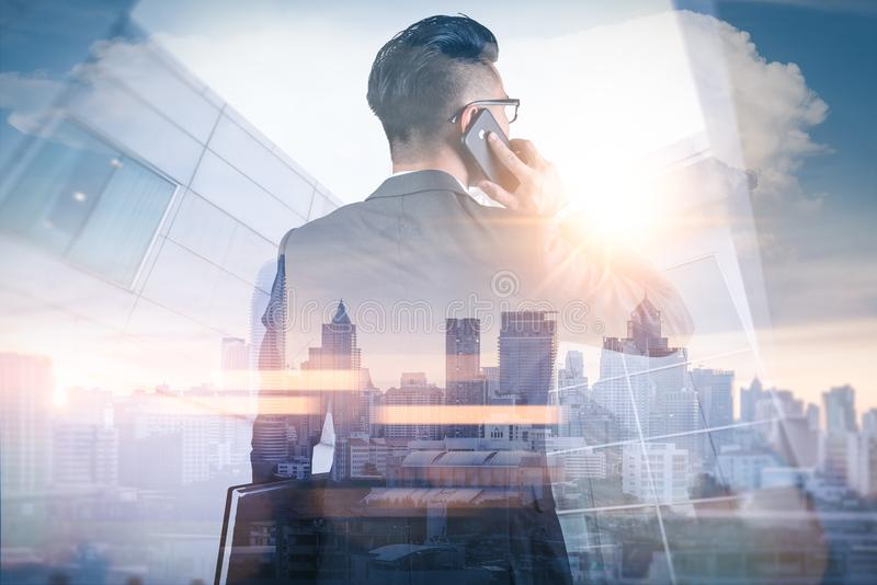 La imagen de la exposición doble del hombre de negocios usando un smartphone durante salida del sol cubrió con imagen del paisaje imagenes de archivo