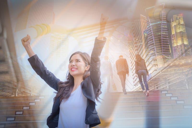 La imagen de la exposición doble de la mujer de negocios que sonríe con los brazos sube el cel fotografía de archivo
