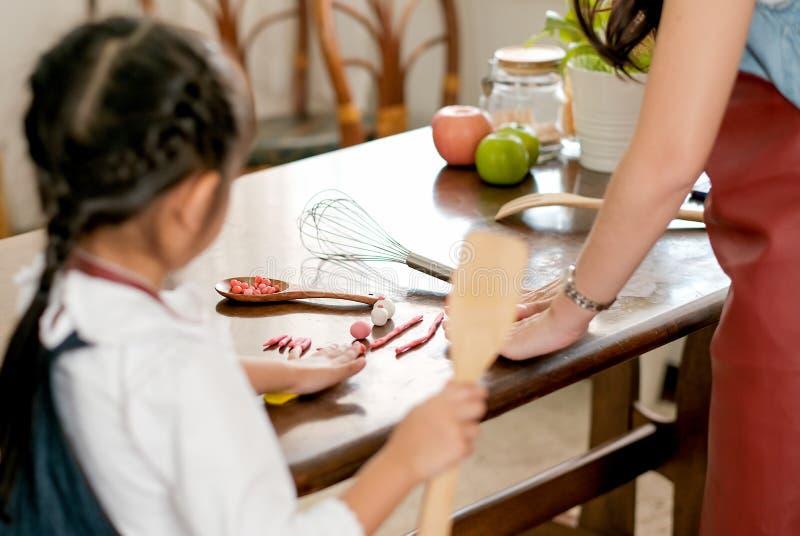 La imagen de falta de definición suave del juego asiático de la niña con la arcilla o el Juego-do así como su madre en la cocina, foto de archivo