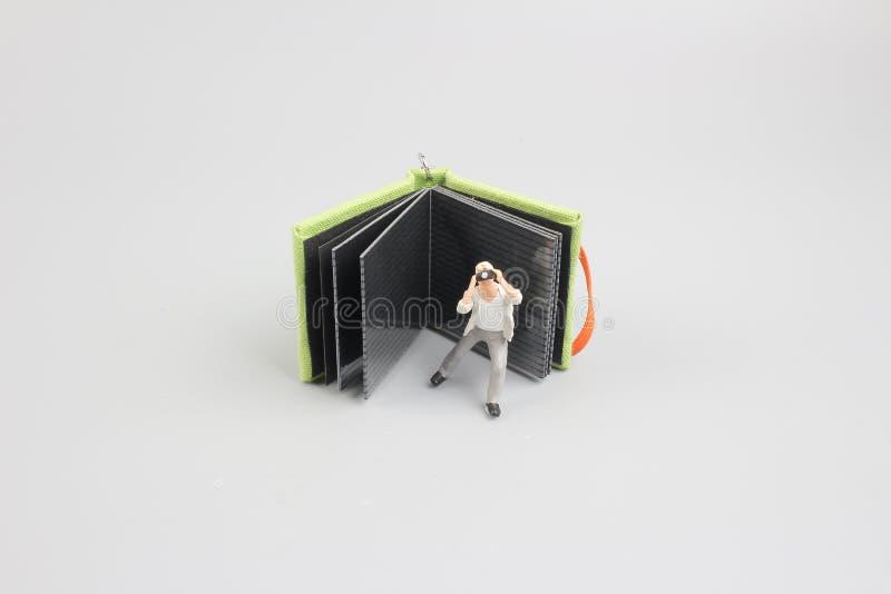 la imagen de la mini figura fotógrafo de las muñecas toma la imagen imágenes de archivo libres de regalías
