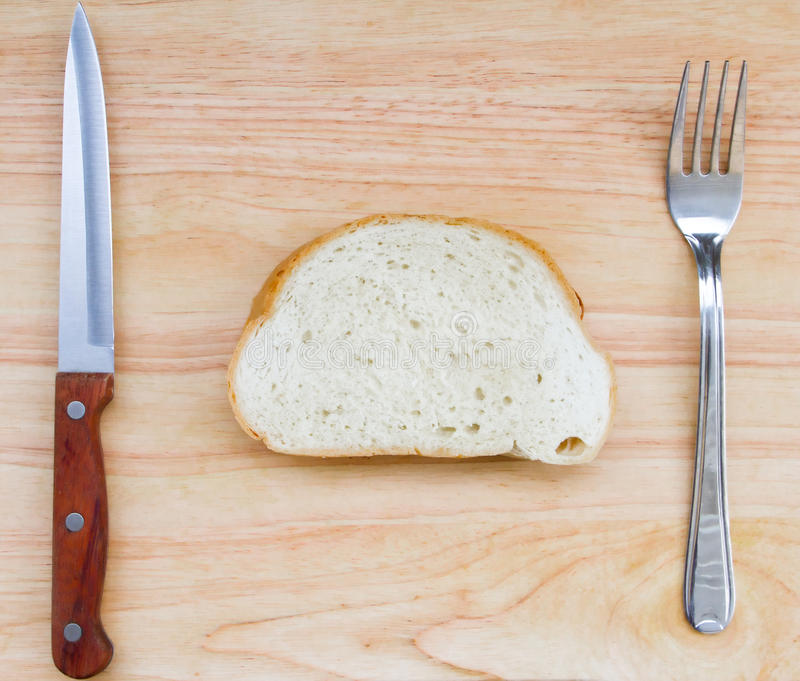 La imagen de la rebanada de pan en una tabla de madera con la bifurcación y el cuchillo imagenes de archivo