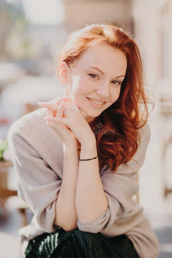 La imagen de las sonrisas modelo femeninas del pelirrojo precioso feliz, tiene piel sana, compone, mantiene las manos juntas, ves fotos de archivo libres de regalías
