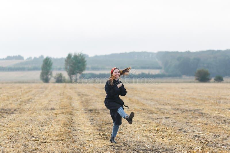La imagen de la mujer alegre feliz que se divierte en campo de trigo, morenita hermosa con aumentado para arriba da disfrutar de  fotografía de archivo libre de regalías