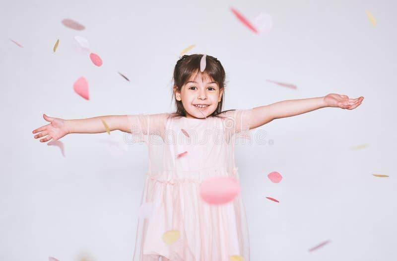 La imagen de la niña bonita que lleva el vestido rosado en Tulle con la corona de la princesa en la cabeza en las manos blancas d imagen de archivo libre de regalías