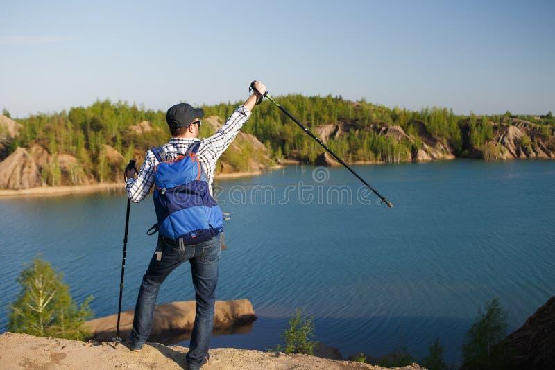 La imagen de la parte posterior del turista joven con la mochila con los brazos aumentó con los bastones en el fondo del paisaje  foto de archivo libre de regalías