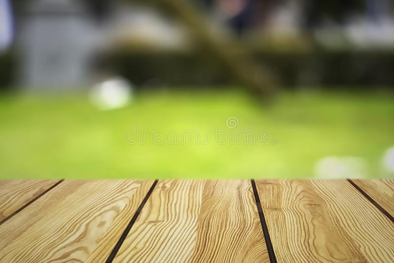 La imagen de la tabla de madera delante del extracto empañó el fondo de luces resturant imagenes de archivo
