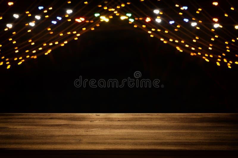 La imagen de la tabla de madera delante del extracto empañó el fondo de oro de las luces de la guirnalda de la ciudad fotos de archivo libres de regalías