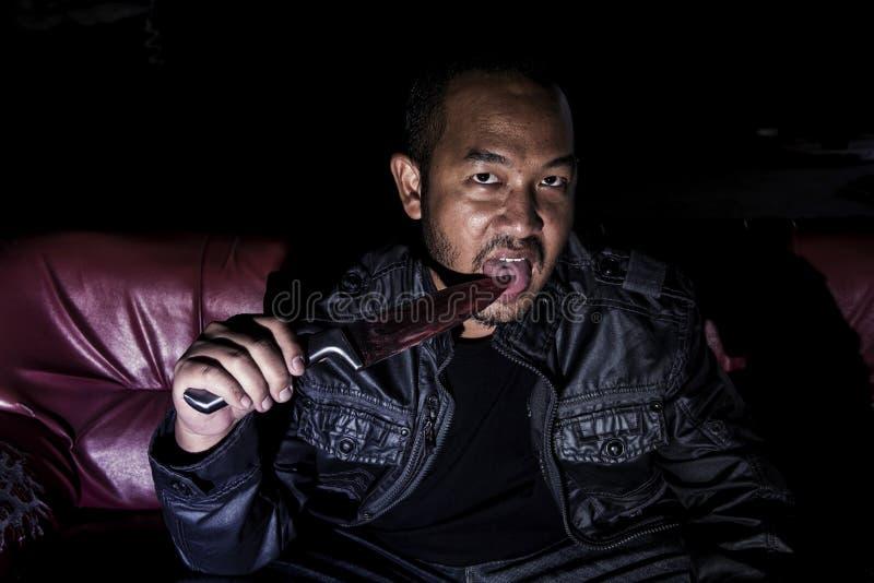 La imagen de un hombre que sostiene un cuchillo sangriento asustadizo imagen de archivo